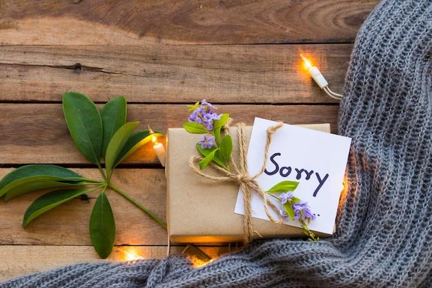 Scrittura a mano della scheda messaggio spiacente con scatola