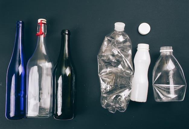 Smistamento dei rifiuti. tre bottiglie di vetro e di plastica vuote sono preparate per il riciclaggio. ridurre riutilizzare riciclare. proteggere l'ambiente. vista dall'alto