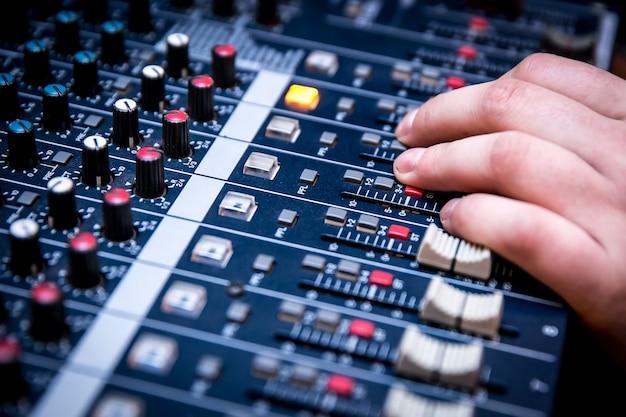 Il responsabile del suono sta lavorando al mixer audio, preparando un nuovo mix di una canzone o lavorando su un evento dal vivo