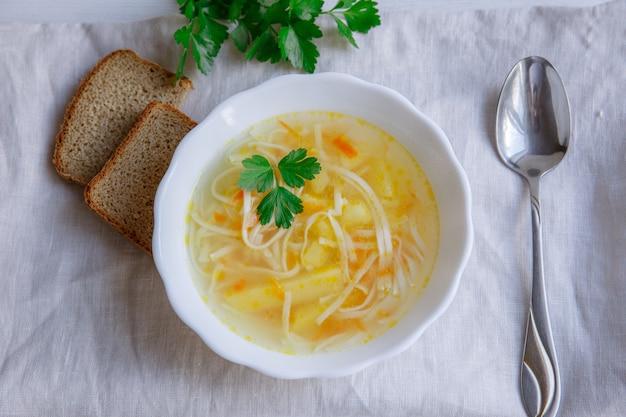Brodo di brodo di pollo zuppa, piatto di zuppa di verdure fresca fatta in casa servita sul tavolo grigio chiaro