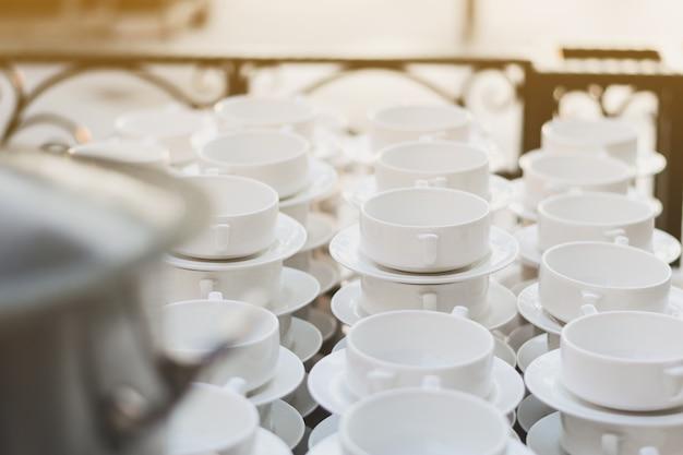 Tazze di zuppa e piatti bianchi sono posti sul tavolo per essere serviti.