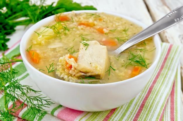 Zuppa di pesce kulesh con miglio, patate e carote e cucchiaio in una ciotola su un tovagliolo, prezzemolo, aneto su uno sfondo di tavola di legno
