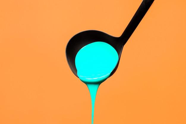 Mestolo di zuppa con vernice su uno sfondo arancione