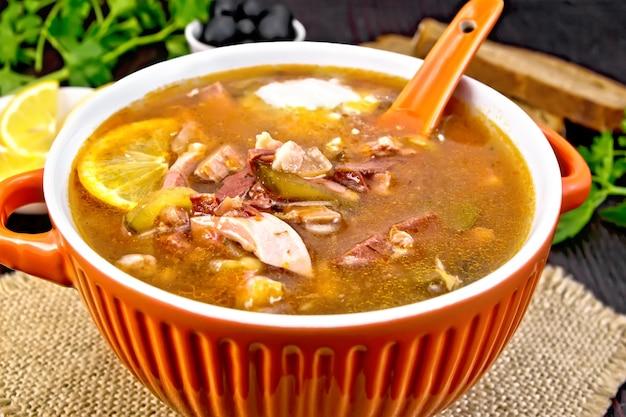 Zuppa di salicornia con limone, carne, sottaceti, olive in salsa di pomodoro, cucchiaio in una ciotola su un sacco su uno sfondo di una tavola di legno scuro