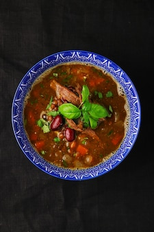 Zuppa con fagioli e carne in una ciotola sul tavolo scuro vista