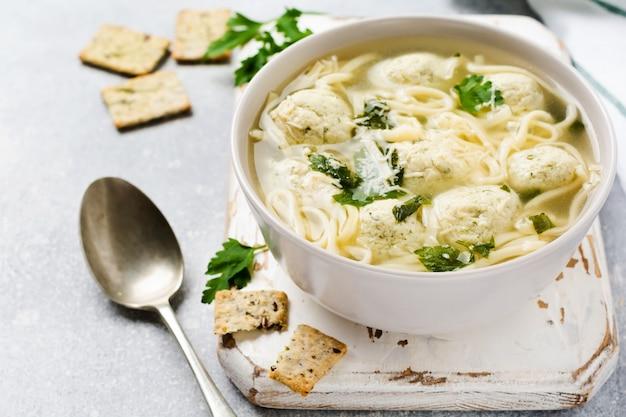 Zuppa con polpette di carne di pollo e pasta d'uovo, parmigiano, prezzemolo in una ciotola di ceramica su uno sfondo di tavolo grigio