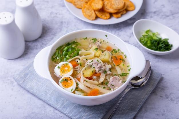 Zuppa con pollo, pasta, patate, uova di quaglia e carote. condite con cipolle e prezzemolo. avvicinamento.