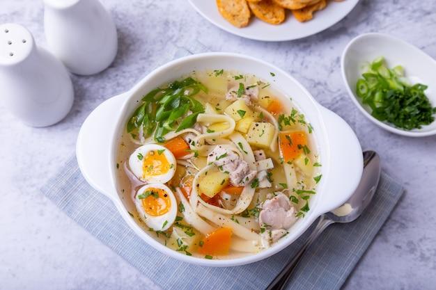 Zuppa con spaghetti di pollo patate uova di quaglia e carote condita con cipolle e prezzemolo primo piano