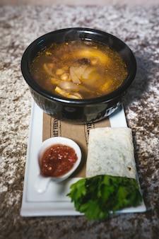 Zuppa con ceci e polpette in un piatto nero.