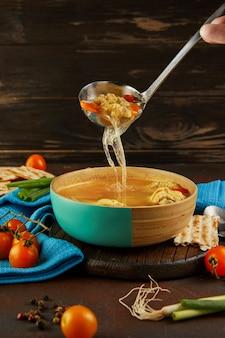 La zuppa con gnocchi matzo e pollo con carote e pomodori viene versata in una ciotola con un mestolo. cibo sano per la pasqua.
