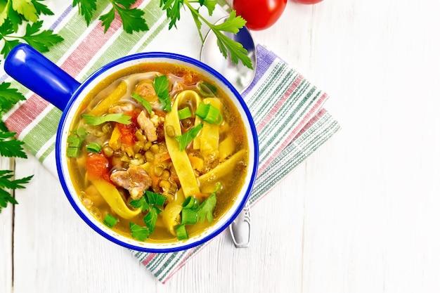 Zuppa con carne, verdure, lenticchie di fagioli mung e tagliatelle in ciotola su un asciugamano su tavola di legno