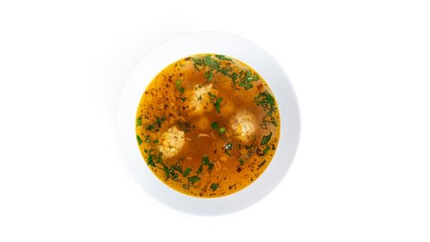 Zuppa con polpette in un piatto fondo bianco isolato