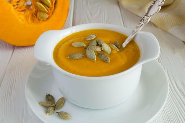 Zuppa con la zucca nel piatto su fondo di legno bianco.