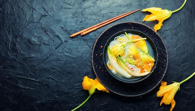 Zuppa con spaghetti di riso e fiori di zucca.zuppa asiatica vegana.copia spazio