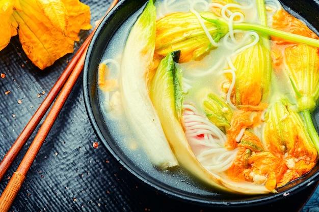 Zuppa con spaghetti di riso e fiori di zucca. zuppa asiatica vegana.