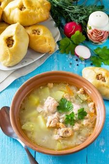 Zuppa con orecchie di salmone e crostate aperte con pesce rosso sullo sfondo di legno della cucina