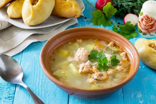 Zuppa con orecchie di salmone e torte aperte con pesce rosso sullo sfondo di legno della cucina