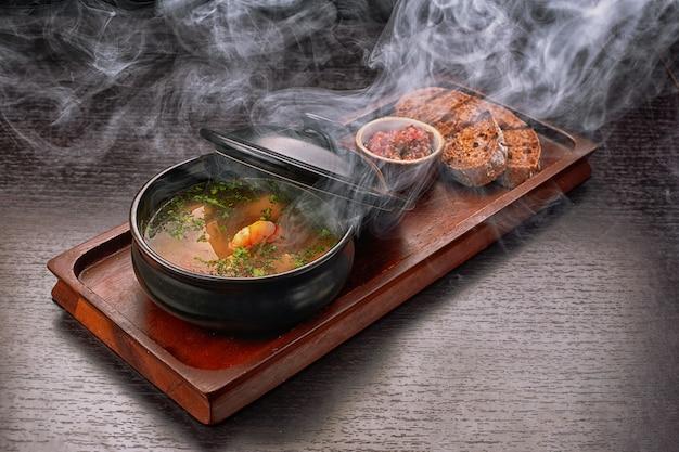 Zuppa di gamberi, salsa, pane, crostini di pane, su una tavola di legno, con affumicatura, vapore
