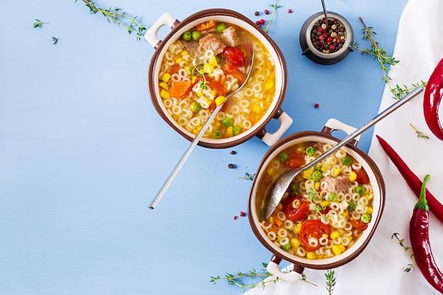 Zuppa con pasta piccola, verdure e pezzi di carne in una ciotola sul tavolo blu. cibo italiano. Foto Premium