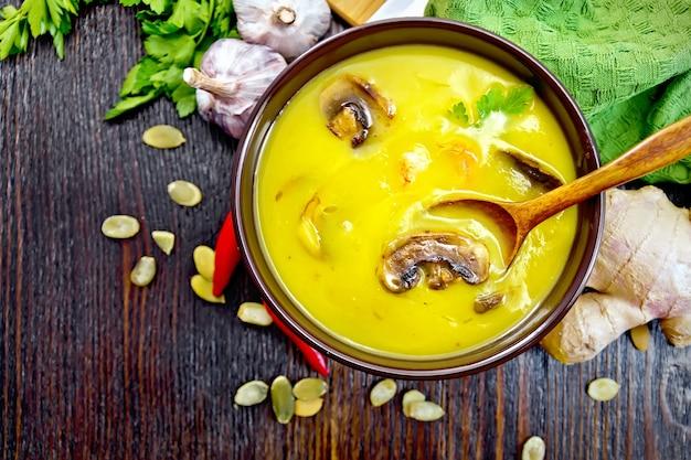 Zuppa di zucca con gamberi e funghi prataioli, un cucchiaio in una ciotola marrone, tovagliolo, prezzemolo, semi di zucca, zenzero su uno sfondo di tavola di legno