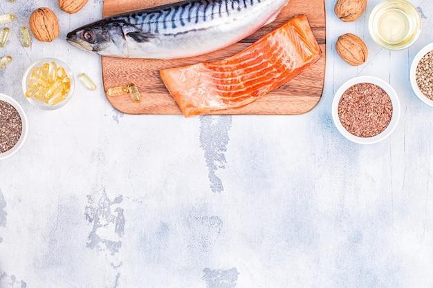 Fonti di omega 3: sgombro, salmone, semi di lino, semi di canapa, chia, noci, olio di semi di lino. concetto di mangiare sano. vista dall'alto con copia spazio.