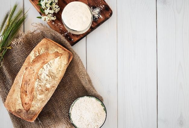 Lievito naturale per la preparazione di pane, farina e pane appena sfornato su un tavolo di legno bianco
