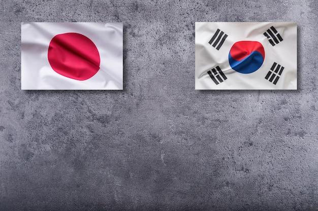 Bandiere della corea del sud e del giappone. bandiera della corea del sud e del giappone su sfondo concreto.