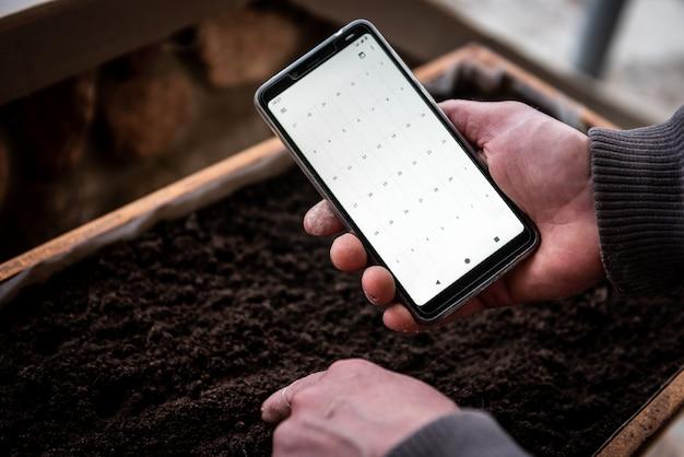 Semina delle piante in calendario. telefono cellulare in mano del giardiniere sul suolo.