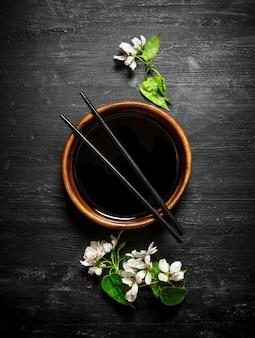 Salsa di soia con un ramo di ciliegio in fiore su fondo in legno nero