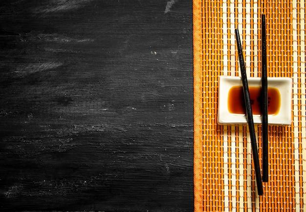 Salsa di soia con bacchette per sushi su uno sfondo di legno nero