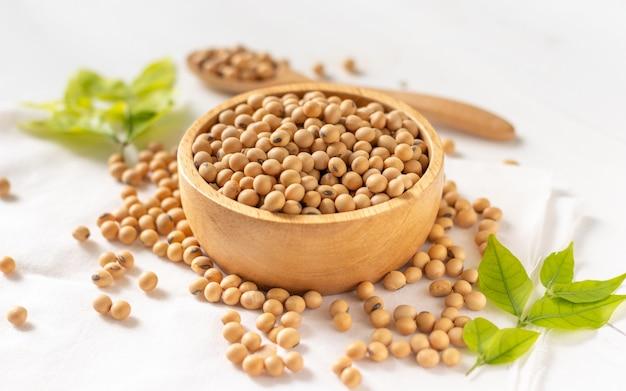 Soia o semi di soia in una ciotola su fondo di legno bianco
