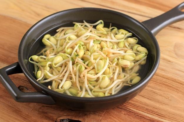 Zuppa di germogli di soia (kongnamul guk) rinfrescante in stile cibo coreano, servita su una ciotola nera, tavolo in legno con cipolla verde affettata sulla parte superiore.