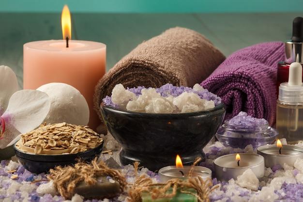 Composizione di accessori spa con fiore di orchidea, ciotola con sale marino, bottiglie con olio aromatico, sapone, scrub, candele e asciugamani su tavola di legno