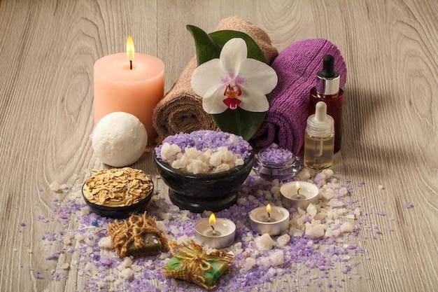 Accessori spa con fiori di orchidea, ciotola con sale marino, bottiglie con olio aromatico, sapone, scrub, candele e asciugamani su tavola di legno