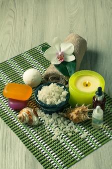 Accessori spa con fiori di orchidea, ciotola con sale marino, conchiglie, bottiglie con olio aromatico, sapone, candele e asciugamano su tovagliolo di bambù
