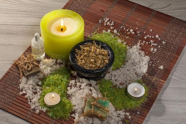 Accessori spa con sapone, ciotola con fiori secchi di camomilla, bottiglia con olio aromatico, sale marino verde e bianco, candele su tovagliolo di bambù
