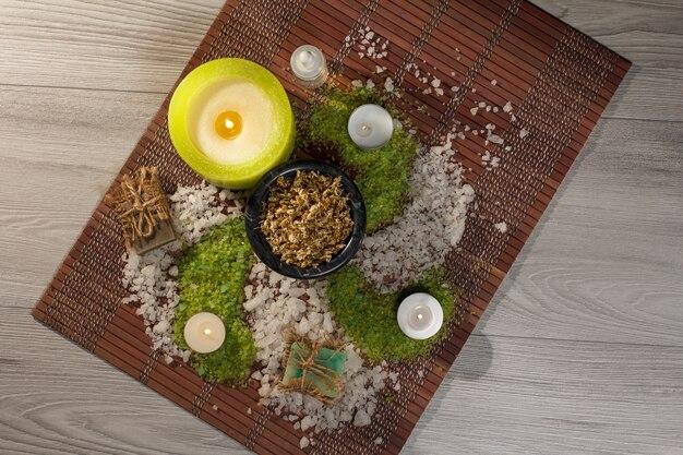 Accessori spa con sapone, ciotola con fiori di camomilla essiccati, bottiglia con olio aromatico, sale marino, candele su tovagliolo di bambù