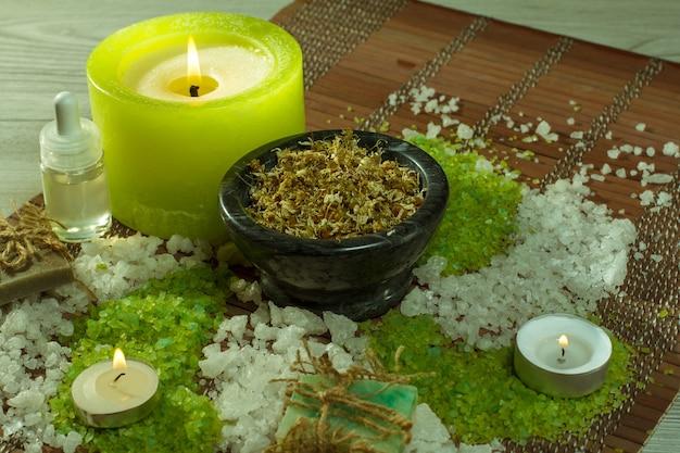 Accessori spa con sapone, ciotola con fiori secchi di camomilla, bottiglie con olio aromatico, sale marino, candele su tovagliolo di bambù e fondo in legno