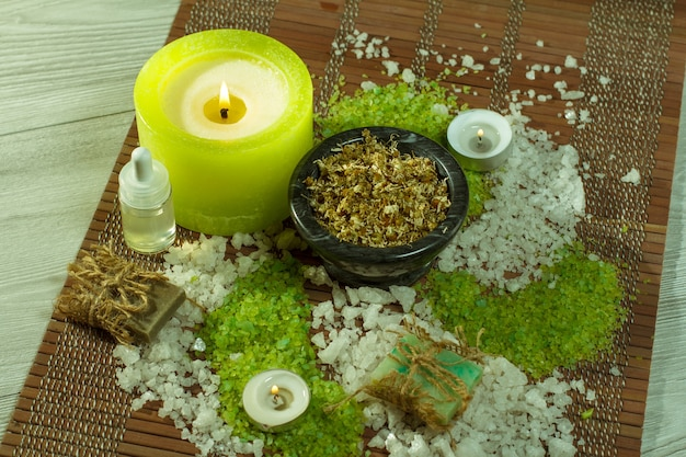 Accessori spa con sapone, ciotola con fiori di camomilla essiccati, bottiglie con olio aromatico, sale marino, candele su tovagliolo di bambù