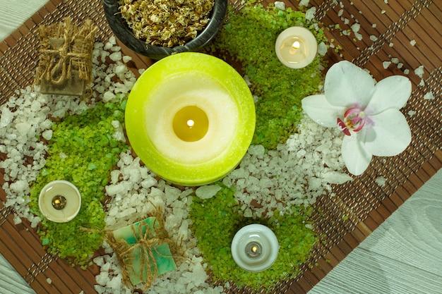 Accessori spa con sapone, fiori di orchidea, ciotola con fiori di camomilla essiccati, bottiglie con olio aromatico, sale marino, candele su tovagliolo di bambù