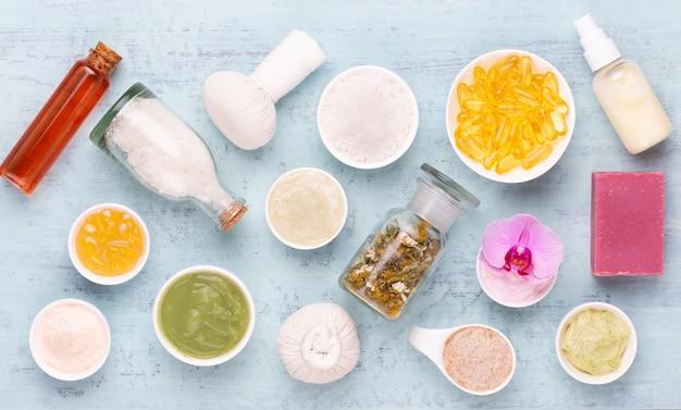 Aromaterapia spa, disposizione piatta di vari prodotti per la cura di bellezza decorati con semplici fiori di orchidea