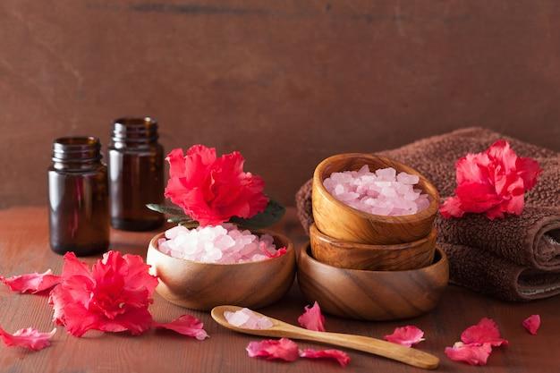 Aromaterapia spa con fiori di azalea e sale alle erbe su sfondo scuro rustico