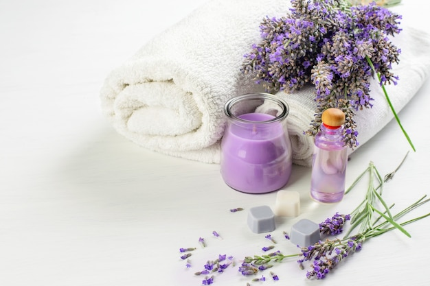 Prodotti aromatici spa. fiori di lavanda, candela, sapone, olio per la pelle e asciugamani bianchi. spa aroma terapia, concetto di assistenza sanitaria.
