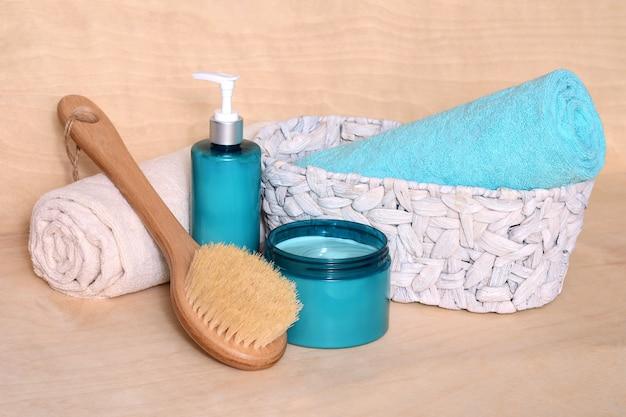 Articoli per il bagno e la spa, impacchi, lozione per massaggi, spazzola per massaggi e asciugamani nel cestino.