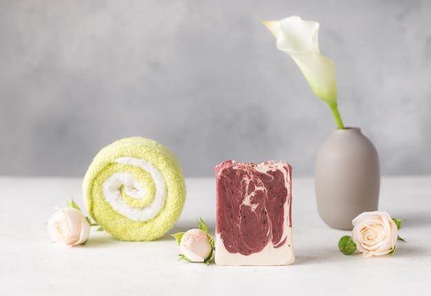 Impostazione della vasca idromassaggio con saponetta naturale fatta a mano, asciugamano, fiori