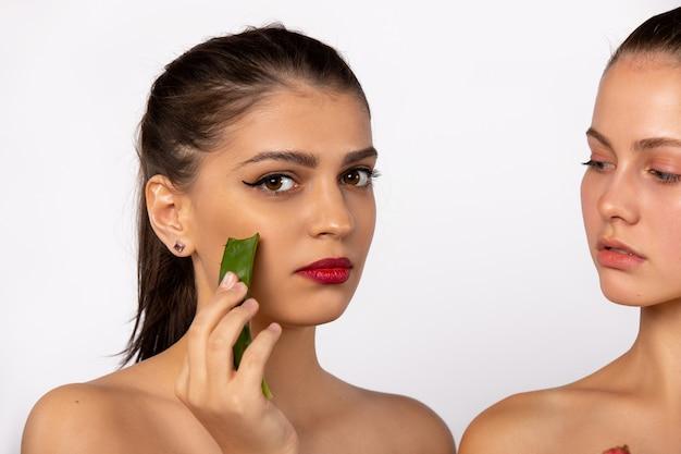 Il concetto di bellezza e della stazione termale ha allargato la foto delle giovani donne con la mascherina di vera dell'aloe isolata sulla parete bianca