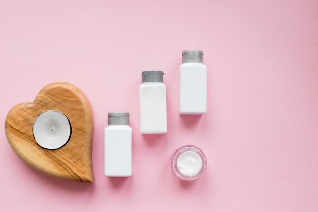 Prodotti di bellezza spa sulla parete rosa. olio di cocco, panna, profumo, candele. concetto del blog di bellezza attributi della procedura spa, crema viso e corpo, fiori di orchidea. retinolo idratante anti invecchiamento
