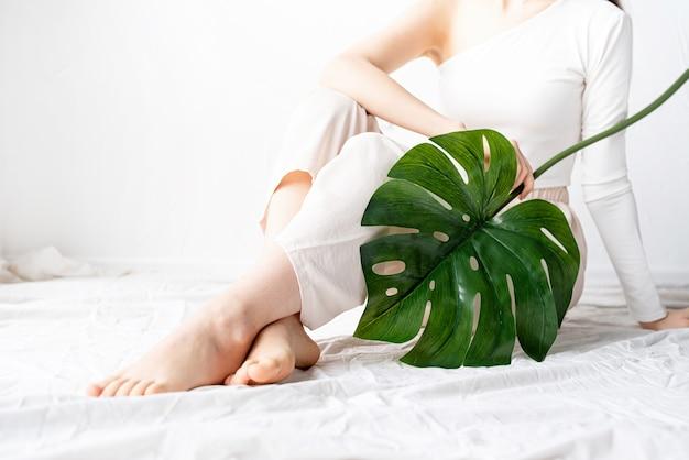 Spa e bellezza. cura di sé e cura della pelle. bella donna felice in vestiti accoglienti che tiene una foglia di monstera verde
