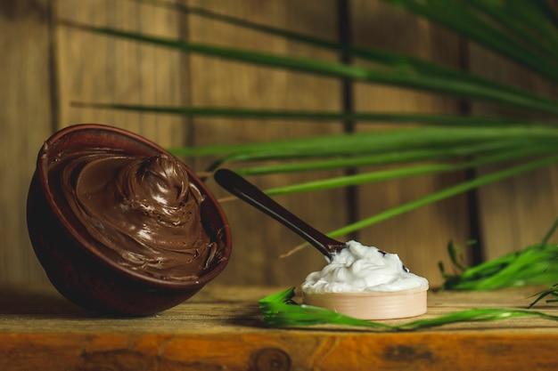 Maschera termale al cioccolato. spa al cioccolato su fondo in legno. concetto di cioccolato spa su uno sfondo di legno