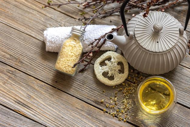 Composizione spa in stile rustico con bollitore, tè e luffa su una superficie in legno.